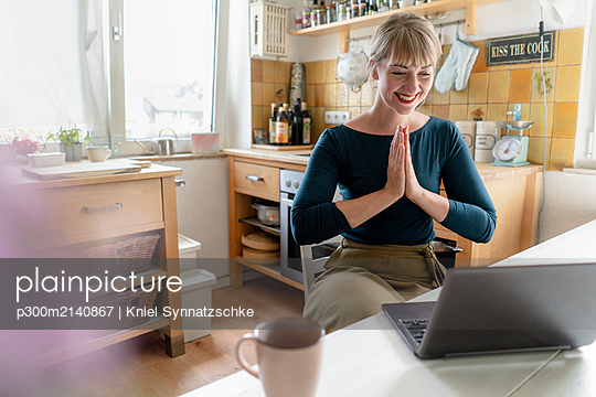 Portrait of laughing woman with laptop practicing yoga in the kitchen - p300m2140867 von Kniel Synnatzschke