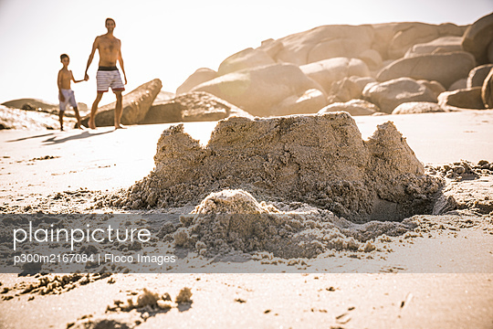 Sand castle on the beach with father and son walking in background - p300m2167084 by Floco Images
