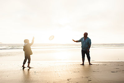 Father and son playing with Frisbee while standing on shore at beach against sky - p1166m1509696 by Cavan Images