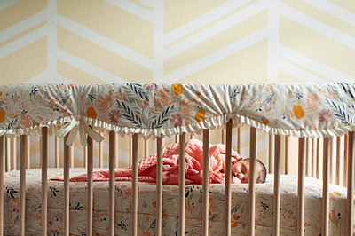 Newborn baby girl wrapped up in blanket sleeping in her crib at home - p1166m2136697 by Cavan Images
