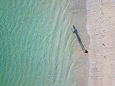 Indonesia, Bali, Melasti, Aerial view of Karma Kandara beach, woman standing on the beach - p300m2042597 by Konstantin Trubavin