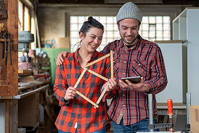 Portrait of happy craftswoman and craftsman holding tablet and yardstick in their workshop - p300m2171229 by Robijn Page