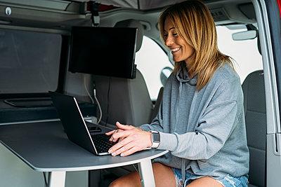 Smiling businesswoman working on laptop in van - p300m2276940 by Manu Padilla Photo