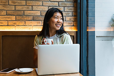 Young woman with laptop looking away holding coffee cup at cafe - p300m2282775 by NOVELLIMAGE