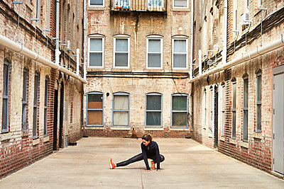 Female runner stretching in urban alley before running, Boston, Massachusetts, USA - p343m1577978 by Josh Campbell