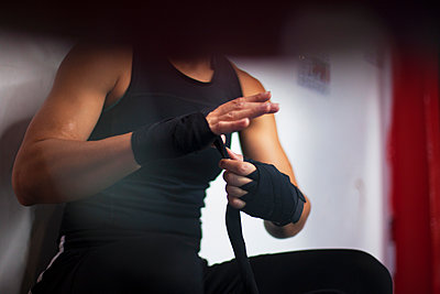 Female boxer putting on handwrap - p429m2050574 by Image Source