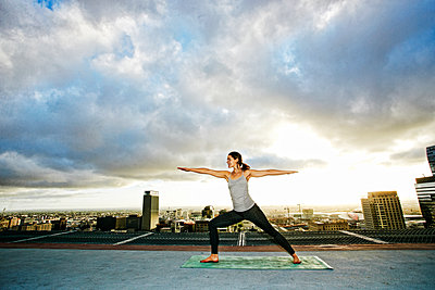 Caucasian woman stretching on urban rooftop - p555m1304819 by Peathegee Inc