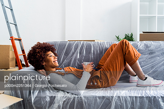 Smiling woman with coffee cup lying on sofa at new home - p300m2251364 by Giorgio Fochesato