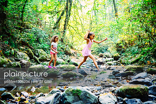 Mixed race sisters exploring stream - p555m1306234 by Inti St Clair
