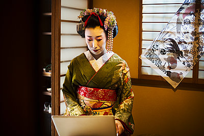 A woman dressed in the traditional geisha style, wearing a kimono and obi, with an elaborate hairstyle and floral hair clips, with white face makeup with bright red lips and dark eyes using a laptop computer.  - p1100m1185739 by Mint Images