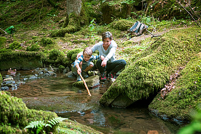 Mother and little son crouching at edge of a brook - p300m1470016 by Dirk Kittelberger