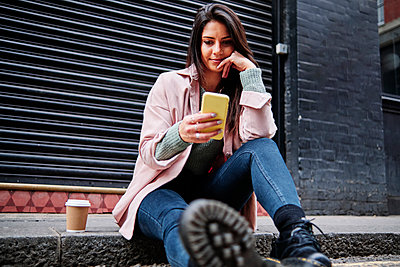 Beautiful woman with coffee cup using mobile phone while sitting on sidewalk - p300m2273671 by Angel Santana Garcia