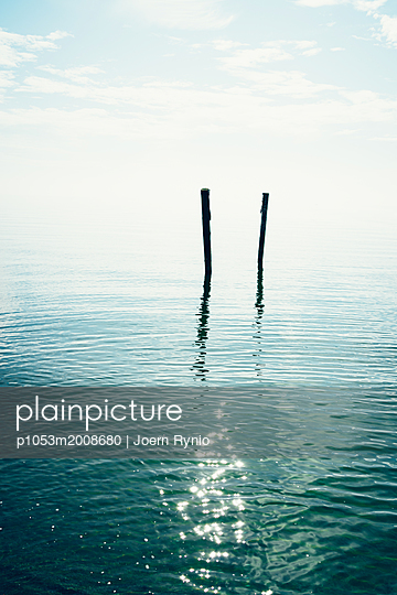 View on calm lake in cloudy summer day - p1053m2008680 von Joern Rynio