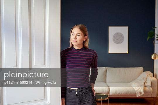 Junge Frau lehnt an Türrahmen - p1124m1589214 von Willing-Holtz