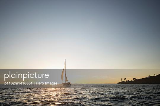 Sailboat on tranquil sunset ocean