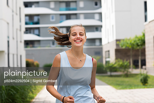 Smiling young woman jogging - p924m2292504 by Sigrid Gombert