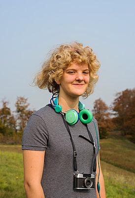 Mädchen mit Kopfhörern und Fotoapparat, Portrait - p1132m1503156 von Mischa Keijser