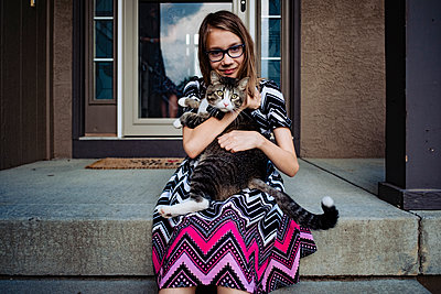 a pre teen girl holding her gray cat on the front porch - p1166m2208023 by Cavan Images