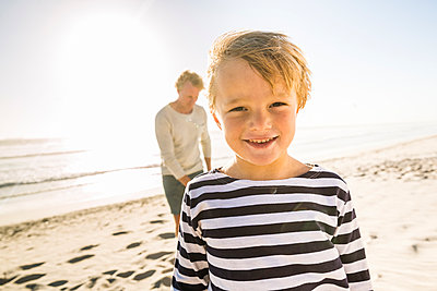 Portrait of smiling boy on the beach with father in background - p300m2167526 by Floco Images