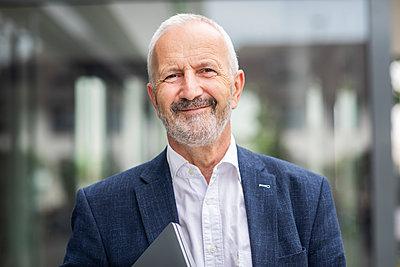 Happy senior businessman with laptop - p300m2294144 by Sigrid Gombert