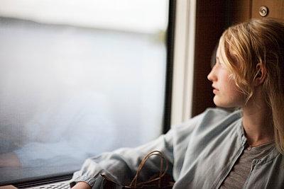 Teenage girl looking through window - p312m1472489 by Christina Strehlow