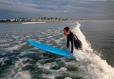 A Boy Surfs At Nahant Beach In Nahant, Massachusetts - p343m1416084 by Laurie Swope