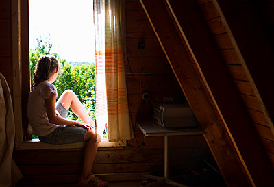Teenage girl sitting on bedroom windowsill looking out at sunlight - p429m1495968 by Chuvashov Maxim