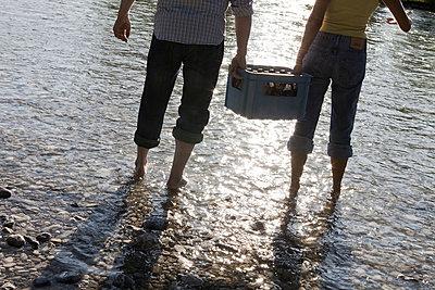 Mann und Frau tragen Kiste Bier in der Isar - p4903145 von T-Pool