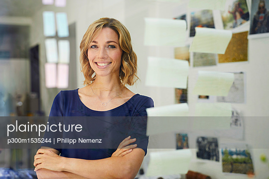 Portrait of smiling blond woman, pane with notepads - p300m1535244 by Philipp Nemenz