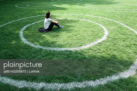 Single woman sitting in a chalk circle in the meadow, social distancing  - p851m2205873 by Lohfink