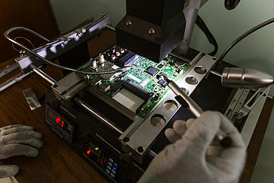 Electronics expert examining damaged circuit board at repair shop - p300m2226829 by DREAMSTOCK1982