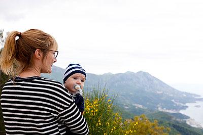 Mutter hält Baby auf dem Arm und blickt in die Ferne - p795m2158218 von JanJasperKlein