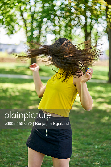 Young woman in park tossing her hair - p300m1587270 von Benjamin Egerland