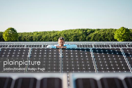 Mature man standing in solar plant - p300m2004609 von Robijn Page