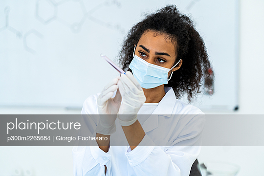 Female researcher examining test tube in laboratory during pandemic - p300m2265684 by Giorgio Fochesato