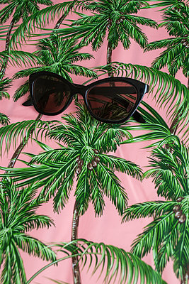Sunglasses on a palm tree patterned tablecloth - p1199m2100315 by Claudia Jestremski