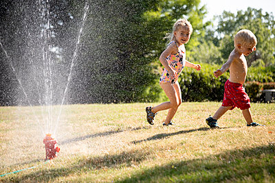 Portrait of a young girl and boy playing in a backyard sprinkler - p1480m2148175 by Brian W. Downs