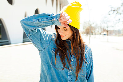Spain, Barcelona, young woman wearing yellow cap and denim shirt - p300m1587041 by Valentina Barreto