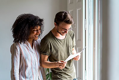 Happy male and female entrepreneurs looking at document while standing near window at office - p300m2264489 by VITTA GALLERY