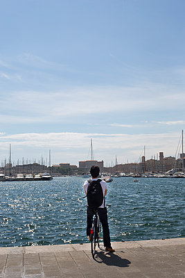 Biker looking at the harbour of Marseille - p445m1153173 by Marie Docher