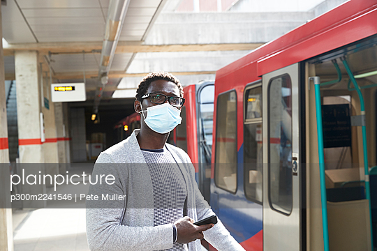 Male professional with mobile phone looking away while standing at railroad station - p300m2241546 by Pete Muller