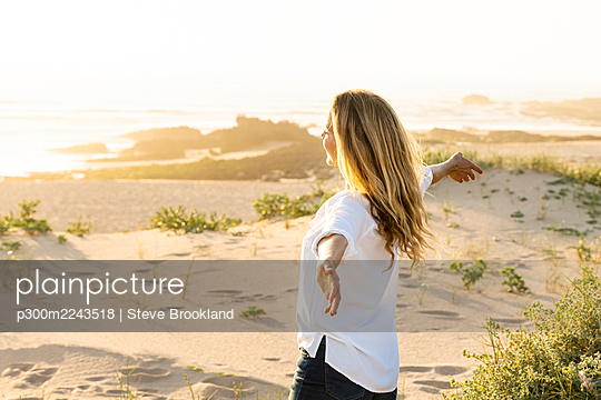Carefree woman with arms outstretched standing on sand - p300m2243518 by Steve Brookland