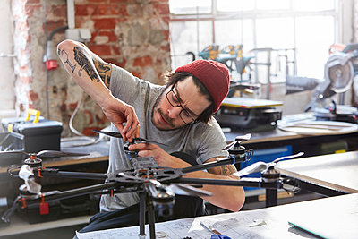 Male designer with tattoos assembling drone in workshop - p1023m1486414 by Rafal Rodzoch