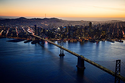 Aerial view of Bay Bridge and illuminated cityscape during sunset - p1166m1164456 by Cavan Images