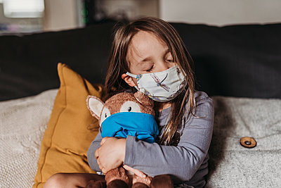 Preschool age girl with mask on cuddling stuffed animal with mask - p1166m2207781 by Cavan Images