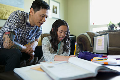 Father helping daughter with homework - p1192m1157992 by Hero Images