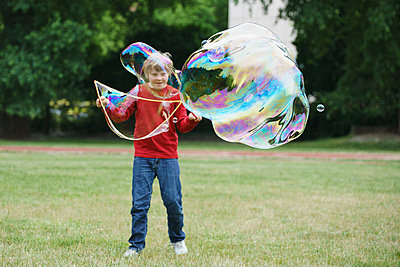 Boy playing with soap bubbles in back yard - p301m1180575 by Halfdark