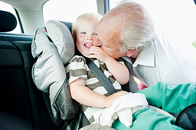 Grandfather kissing grandson in cheek - p312m1164638 by Rebecca Wallin