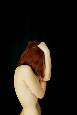 Nude woman holding her head - p4130069 by Tuomas Marttila