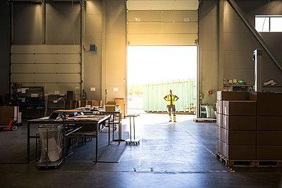 Full length of senior warehouse worker standing at storage room doorway - p426m2018797 by Maskot